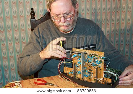 Senior performing do it yourself repair of electronics