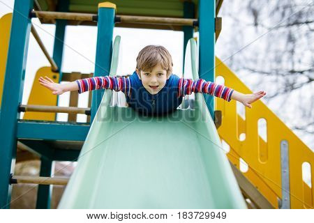 Happy blond kid boy having fun and sliding on outdoor playground. Funny joyful child smiling and climbing on slide. Summer, spring and autumn leisure for active kids. Boy in colorful casual clothes