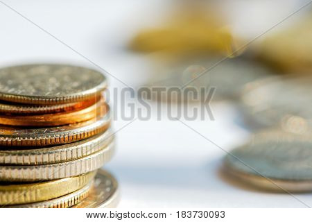 Golden and silver coins in a stack against a blurred background. Business finance and money concept