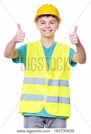 Emotional portrait of handsome caucasian teen boy wearing safety yellow hard hat. Happy child making thumbs up gesture and looking at camera. Funny cute guy - engineer.