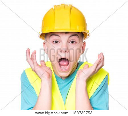 Emotional portrait of handsome caucasian teen boy wearing safety jacket and yellow hard hat. Shocked child looking at camera, isolated on white background. Funny cute guy.