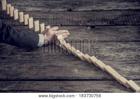 High angle view image of a businessman preventing dominoes from crumbling with palm on an old wooden table retro effect faded look.