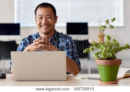 Young Asian entrepreneur smiling confidently while sitting alone at a desk in a modern office working on a laptop, with greenery around him