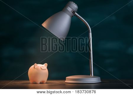 Cute piggy bank on illuminated surface under lamp