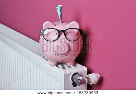 Cute piggy bank with glasses on pink background