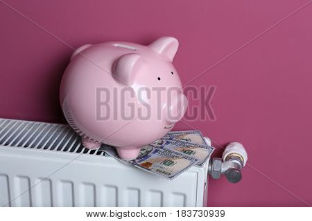 Cute piggy bank with dollars on pink background