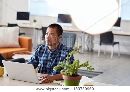 Young Asian designer looking deep in thought while sitting alone at a desk in a modern office working on a laptop