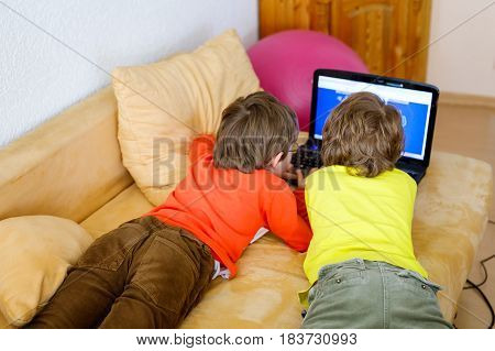 Happy little brothers, adorable kid boys watching television while lying. Funny children enjoying cartoons on notebook, laptop or computer. No faces of people