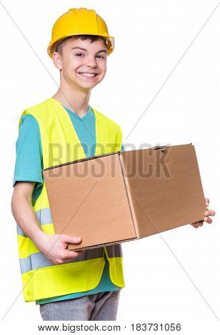 Emotional portrait of handsome caucasian teen boy wearing safety jacket and yellow hard hat. Happy child holding big cardboard box, isolated on white background.