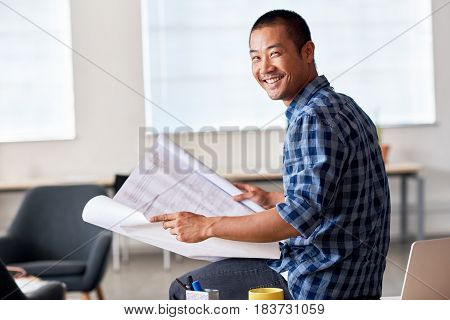Portrait of a casually dressed young Asian architect smiling confidently while reading blueprints in a modern office reading blueprints