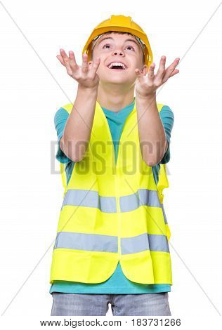 Emotional portrait of handsome caucasian teen boy wearing safety jacket and yellow hard hat. Happy child trying to catch something and looking up, isolated on white background.