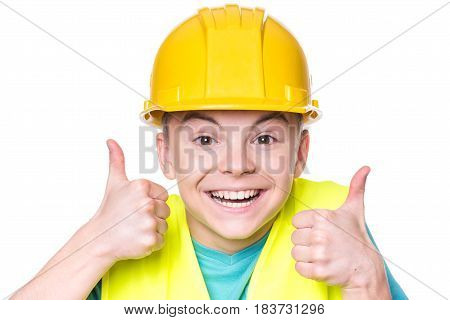 Emotional portrait of teen boy wearing safety yellow hard hat. Happy child making thumbs up gesture and looking at camera. Funny cute guy - engineer, entrepreneur, construction worker or architect.