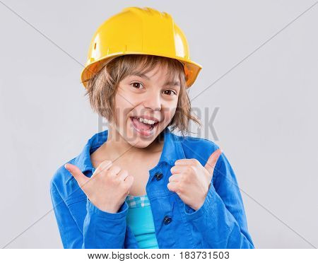 Emotional portrait of attractive girl wearing safety yellow hard hat. Beautiful child making thumbs up gesture and looking at camera. Funny smiling child - engineer, construction worker or architect.