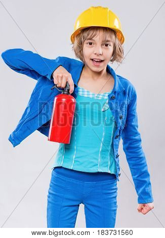 Emotional portrait of attractive caucasian girl wearing safety yellow hard hat. Beautiful happy child holding a fire extinguisher and looking at camera.