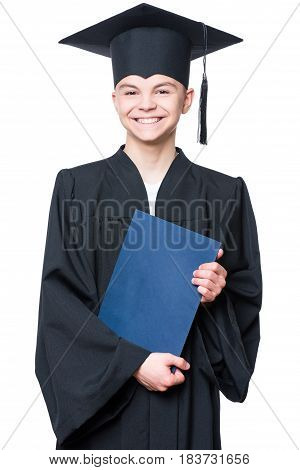 Portrait of a graduate teen boy student in a black graduation gown with hat, holding certificate - isolated on white background. Child back to school and educational concept.