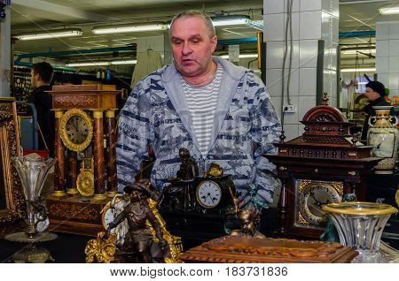 Moscow, Russia - March 19, 2017: Seller of vintage richly decorated wooden, brass and bronze collection mantel clocks at an antic market