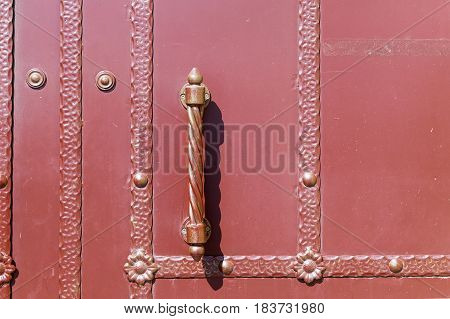 A large closed door with patterns on vertical and horizontal metal bands. Beautiful vertical grip door knobs and a spiral twist. On metal strips metal flowers.