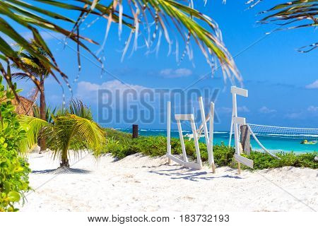 Beautiful white sand and palm trees in Tulum Mexico