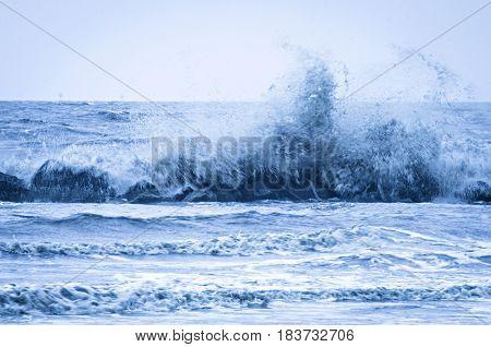 wave crashing into wavaebreaker on louisiana gulf coast