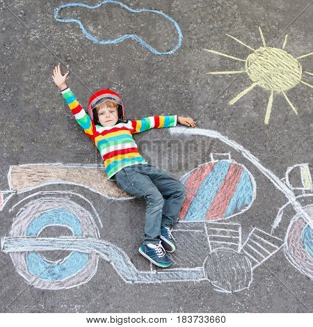 Creative leisure for children: Adorable little child of four years in helmet having fun with motorcycle picture drawing with colorful chalks. Children, lifestyle, fun concept.