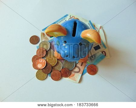 piggy bank standing on money and coins