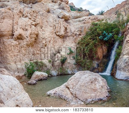 The journey through the reserves Ein Gedi. Adorable waterfall among rocks parched desert