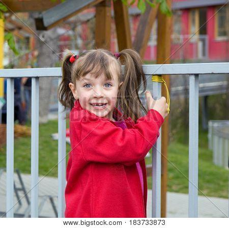 Happy littke girl playing near metal fence