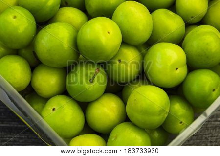 Green sour plums in the plate, excellent taste of green plums