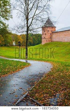 Autumn architecture landscape - Novgorod Kremlin fortress tower in cloudy rainy autumn weather in Veliky Novgorod Russia. Architecture view of Veliky Novgorod Kremlin and autumn park