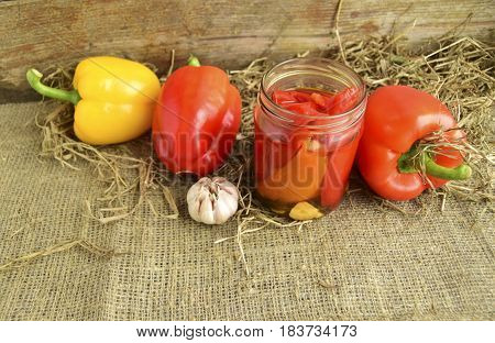 Pickled peppers are in a glass jar. Fresh red and yellow sweet pepper is on a table.