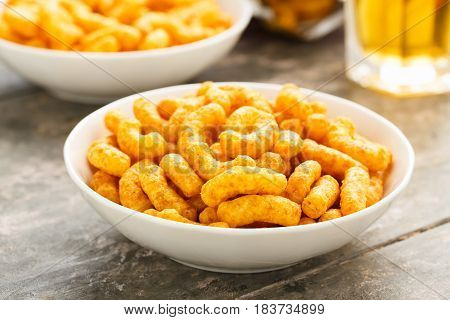 Peanut puffs in a small bowl on a wooden ground