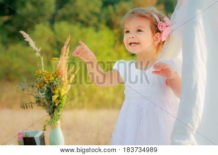Little Girl Smiles And Shows Finger Upward. A Girl In A White Wigwam Or Play Tent, Children's Play H