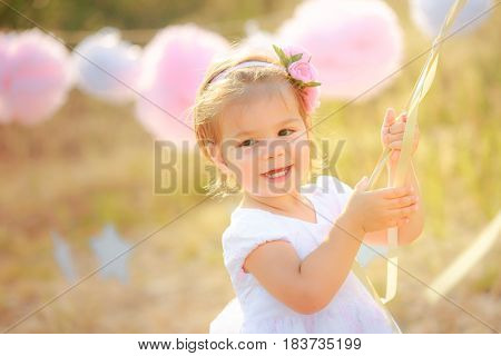 Happy baby on birthday celebration. A girl in a white dress smiles against a background paper pompons.