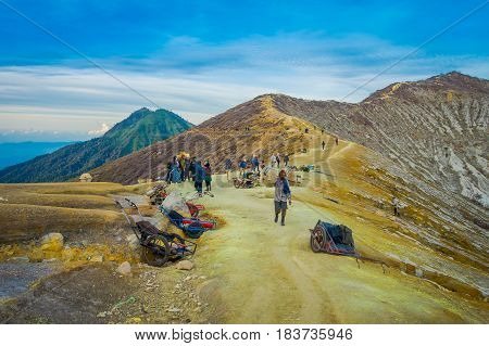 KAWEH IJEN, INDONESIA - 3 MARCH, 2017: Local miners carrying loads of yellow sulfur rocks up mountain side, tourist hiking attraction located inside volcanic crater, spectacular nature.