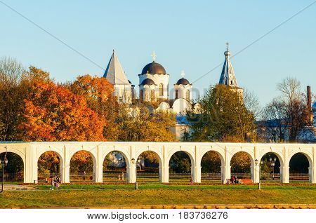Veliky Novgorod, Russia. Architecture landscape - arcade of Yaroslav Courtyard ancient St Nicholas cathedral and people walking along in Veliky Novgorod Russia