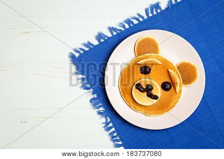 Baby pancakes in a pink plate on a blue towel with space for text