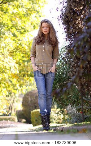 Young blonde woman in blue jeans in autumn park