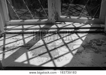 black and white image of old wooden aged peeled paint windowsill with grid shadow