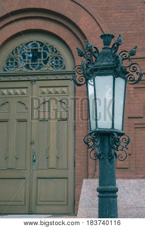 entrance front side of on old brick church with vintage lantern and wooden door
