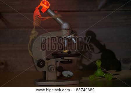 concept image that show process of scientific discovery with sceleton looking at microscope. braind is boiling and turning red