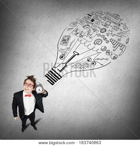 Young businessman holding old alarm clock on sketch background