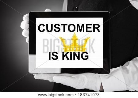 Close-up Of A Waiter Holding Digital Tablet Showing Customer Is King On Screen