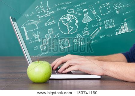 Close-up Of A Man Using Laptop Computer With Green Apple On Desk