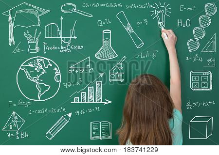 Rear View Of A Girl Drawing On Green Chalkboard