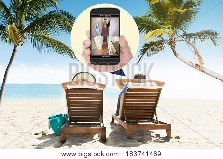 Couple Sitting On Lounge Chair At Beach With Home Security Cameras Viewed On Mobile Phone