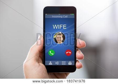 Close-up Of A Hand Holding Smart Phone With Wife's Incoming Call On Display