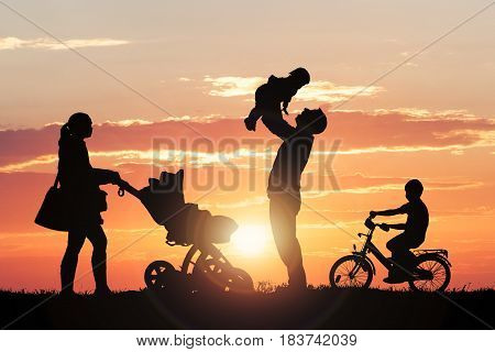Family Silhouette Enjoying At Park Against Dramatic Sky During Sunset