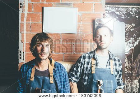 Two young handsome men in working clothes at workshop.