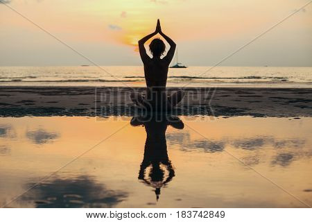 Silhouette yoga woman meditating at the sea shore.