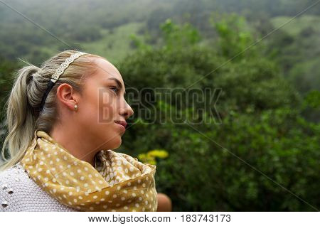 Beautiful young blond contemplative woman in a forest enjoying nature